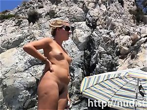 Spy cam shot of a super hot nudist babe tanning on the beach